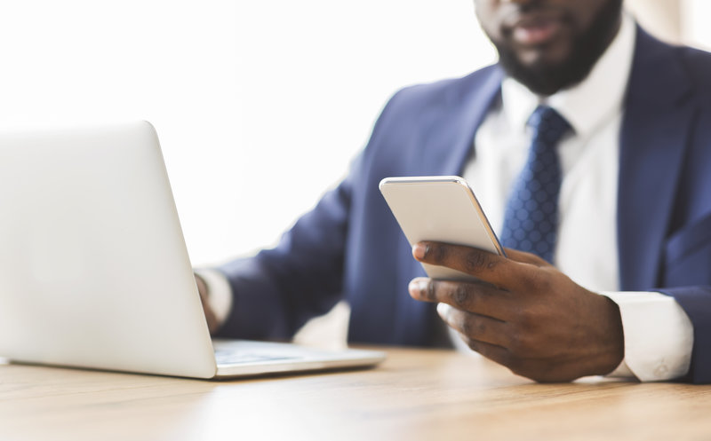 African american businessman using cellphone at workplace, cropped, empty space